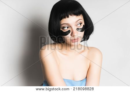 beautiful young girl with black hair looking away, under the eyes of black silicone patches