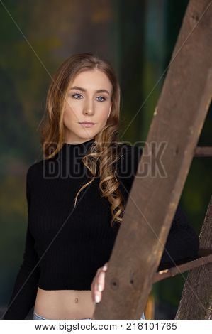Beautiful pretty young woman standing leaning on the ladder. indoor. Looking away. Selective focus. Close-up portrait. Studio photo.