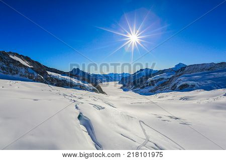 Winter mountains with snow cornice and beautiful blue sky with clouds in cold sun day. Caucasus Mountains region Dombay. View from top of Mount Musa Achitara