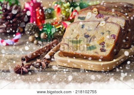 Delicious rum fruit cake for Christmas celebration on wood table background. Fruit cake in side view, copy space with snowfall. Concept to present homemade fruit cake, traditional dessert for Xmas party. Homemade fruit cake ready to served.