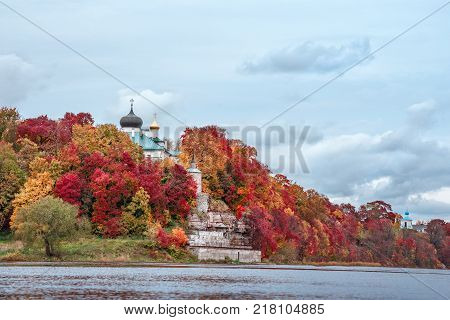 Ancient Christian monastery in colorful autumn Park on the banks of the river on a background of the cloudy sky
