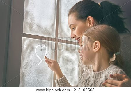 Happy loving family sitting by the window and drawing a heart on frozen glass. Mother and child creating decorations. Concept of love and care.