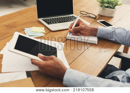 Unrecognizable african-american businessman working on digital tablet and writing in notebook in modern office, side view, copy space