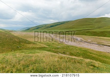 sheep near the bed of a mountain river, flock of sheep grazing in a hill on a green meadow, grazing sheep on the green hills of Assy Kazakhstan plateau.