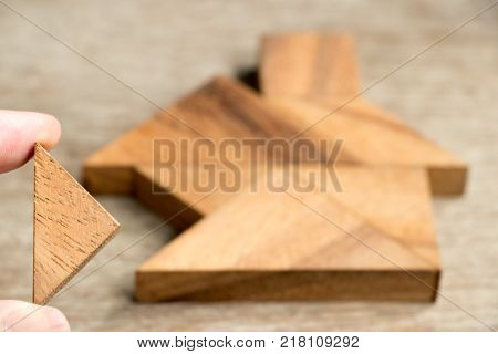 Wood tangram puzzle wait to fulfill in home shape for build dream home happy life property investment house loan concept