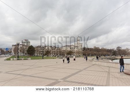 Russia Novorossiysk - October 28.2017: People walk along the embankment named after Admiral Serebryakov. House with a spire - one of the 7 buildings of the ensemble Heroes ' square. Cloudy autumn day