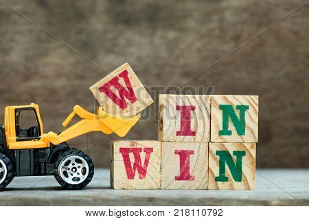 Yellow toy bulldozer hold letter block W to complete word win win on wood background