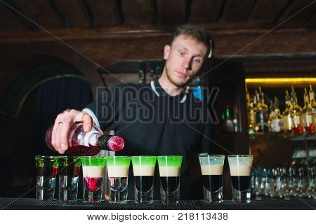The barman creates alcoholic shots. The barman pours an alcohol in the glasses for the show