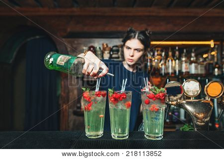 The girl bartender makes a beautiful alcoholic fruit cocktail. The barman creates a cocktail at the pub