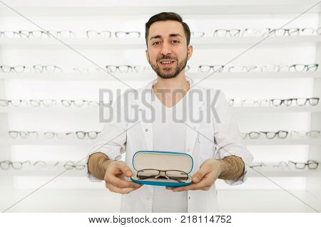 Man seller, dressed in white uniforms holding a box with new glasses standing in the middle of the ophthalmic shop
