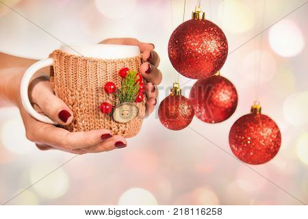 Close up of winter holiday cup in knitted vintage craft cupholder with christmas decorations in hands of woman with beautiful festive red manicure and New Year hanging balls. Horizontal color photo