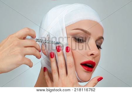Woman get injection. Beautiful woman after plastic surgery with bandaged face. Beauty, Fashion