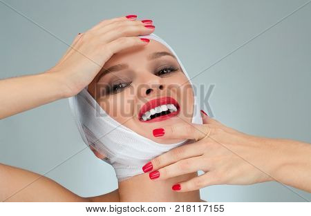 Beauty, Fashion and Plastic Surgery concept. Beautiful woman after plastic surgery with bandaged face.