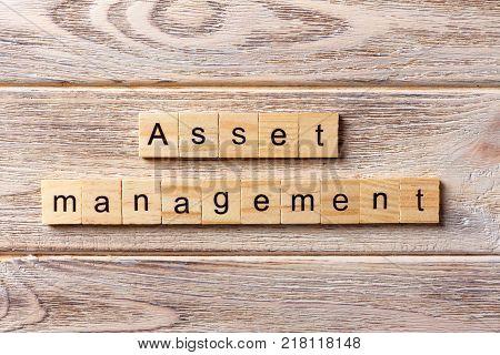 Asset Management word written on wood block. Asset Management text on table concept.