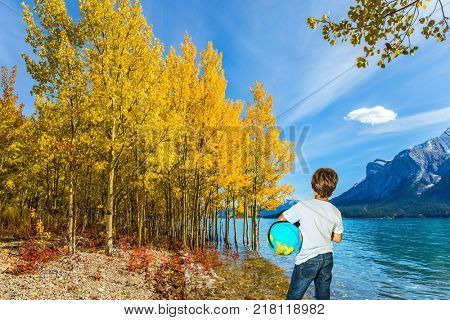 Indian Summer in the Rockies of Canada. Exquisite Abraham Lake with turquoise water. Nine-year-old boy in jeans with a globe in his hands admires the lake. Concept of ecological and active tourism