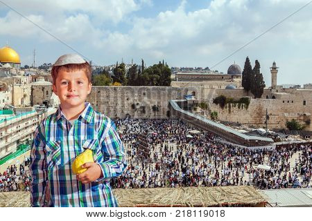 Autumn Jewish holiday Sukkot.  The greatest shrine of Judaism is the Western Wall of the Temple. Handsome little boy in skullcap with etrog