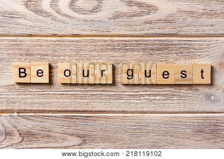 Be our guest word written on wood block. Be our guest text on table concept. poster