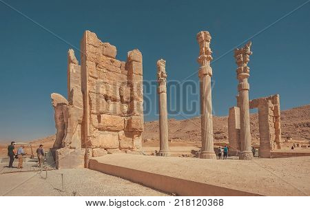 PERSEPOLIS, IRAN - OCT 22, 2017: Gates with columns and impressive ruins to abandoned city and tourists walking past monuments on October 22, 2017. Persepolis was capital of Achaemenid Empire 550 - 330 BC.