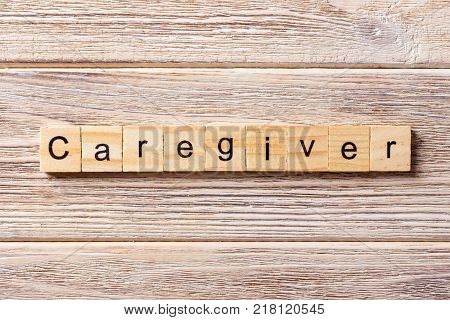 Caregiver word written on wood block. Caregiver text on table concept.