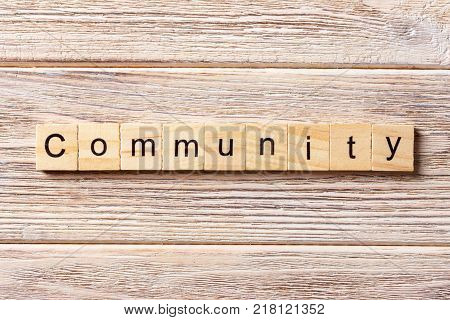 Community word written on wood block. Community text on table concept.