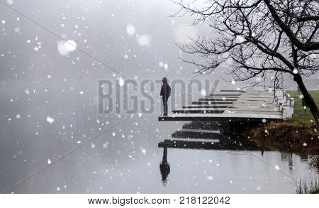 Lonesome man at the lake in snowfall