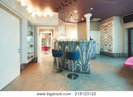 Modern reception interior. Front desk of beauty or spa salon. Entrance hall with tiled counter, comfortable chairs and couch, copy space on white door