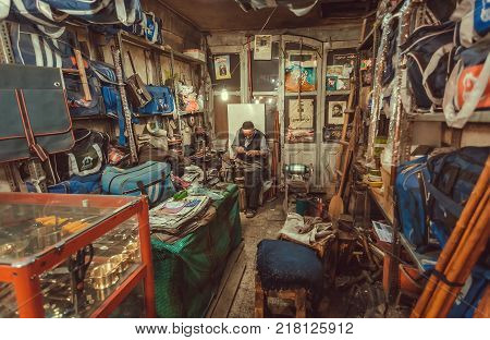 ISFAHAN, IRAN - OCT 14, 2017: Elderly man fixing shoes and bags in his workshop on city market on October 14, 2017. The 3rd largest city of Iran Isfahan is example of Iranian Islamic culture