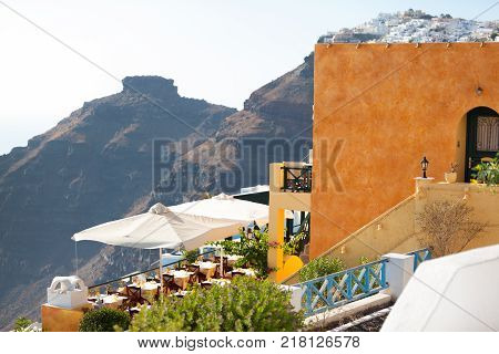 Hotel and restoraunt terasse with famous Skaros rock and Oia village on the background. Santorini island, Greece