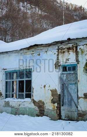 Old abandoned village house during winter period.