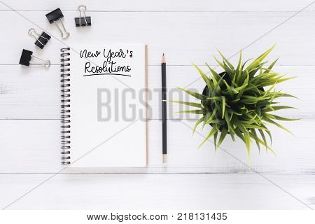 Minimal work space - Creative flat lay photo of workspace desk with New Year Resolution list notebook and wooden pencil on wooden background. Top view flat lay photography. 2018 happy new year concept