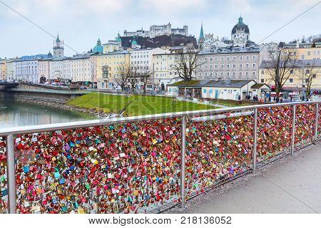 Salzburg, Austria - December 25, 2016: Historic city of Salzburg with love padlocks bridge and Hohensalzburg Festung castle across Salzach river, Austria