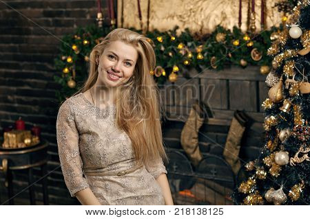 Young woman in a cozy interior of Christmas. The girl sits under a Christmas tree among many gifts. Preparing for Christmas. The concept of a holiday.