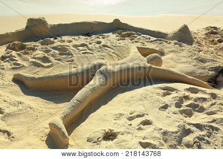 Cute sand sculpture representing a  human laying on the beach  with face down. Aruba island. Caribbean. Fanny background.