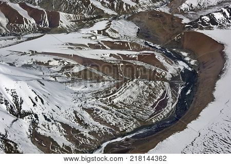 High mountains are the river valley, the blue river is a semicircle located among the high brown slopes covered with snow, Himalayas.