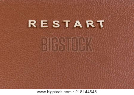 Word restart with abstract wooden letters. Background brown leather, copy space