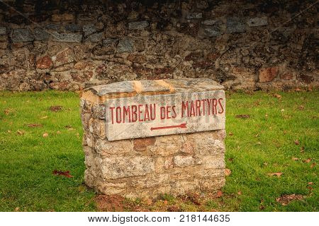 ORADOUR SUR GLANE FRANCE - December 03 2017 : near the cemetery where are buried the victims of the massacre of the population by the Nazis on June 10 1944 a stone panel where it is engraved in red - TOMB of the MARTYRS