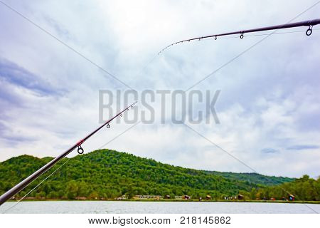 A boat without oars tied with a rope is on the green grass in front of the pond on the background of the countryside and the forest mountain landscape. Landscape on a fishing trip in Sochi, Russia.
