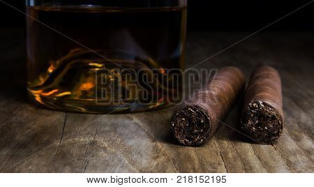 Bottle of whiskey with two cigars standing on an old wooden table