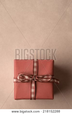 Overhead shot of a square wrapped gift box tied to a bow with gingham check ribbon. Undersaturated to give an aged peach pink hue. Copy space above.