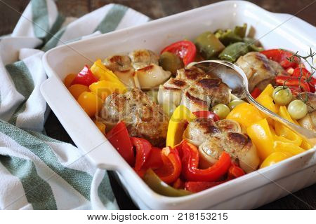 Stewed meat paupiettes with bell peppers in ceramic bakeware rustic style