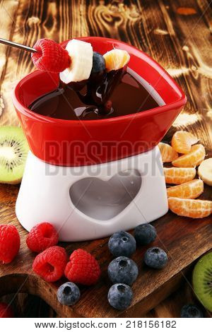 chocolate fondue with fruits assortment on wooden cutting board