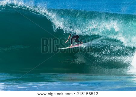 Surfing surfer unidentified tube rides hollow ocean wave overlooking action photo.