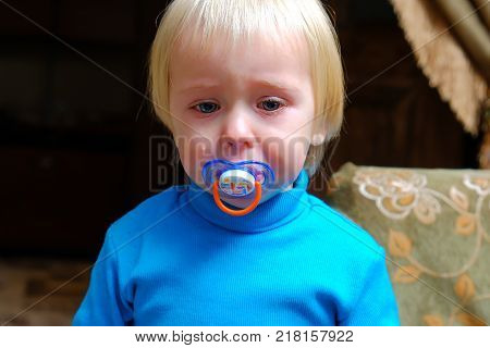 cranky unhappy baby is sitting and crying out loud