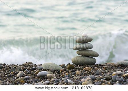 Stones pyramid on Black sea beach symbolizing stability, zen, harmony, balance. Shallow depth of field.