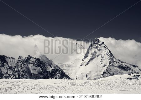 Black and white snowy mountains at sun day view from the ski slope. Caucasus Mountains region Dombay in winter.