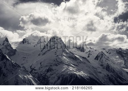Winter snowy sunlight mountains in clouds at nice evening. Caucasus Mountains region Dombay. Black and white toned landscape.