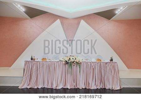 Minimalistic wedding table for the bride and groom. Decorated with roses