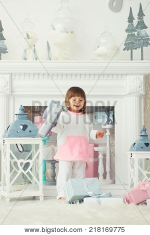A happy smiling little girl is standing with Christmas presents near the New Year tree. Holiday and gifts 2018.