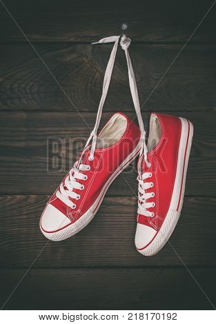 a pair of old red sneakers hanging from a nail on a background of brown wooden wall vintage toning