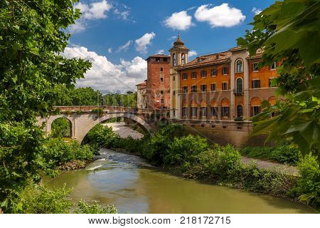 View of the Tiber island or Isola Tiberina with Ponte Fabricio and church Chiesa di San Giovanni Calibita in sunny day, Rome, Italy